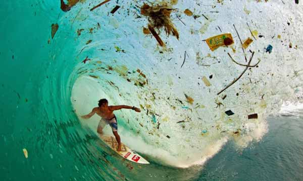 surfer caught in a dirty wave Overconsumption