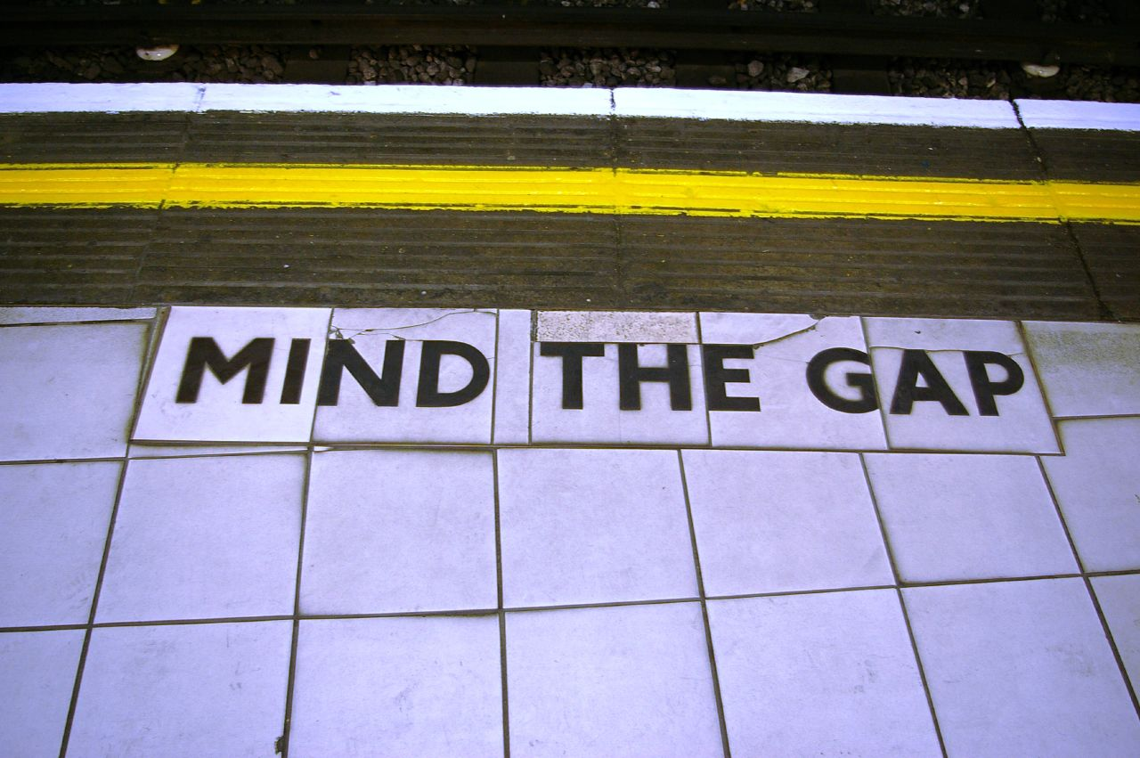 "A subway platform with the words ""mind the gap"" written on the floor"