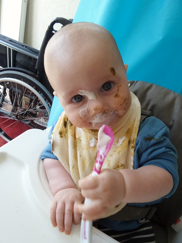 baby in a high chair, covered in green and pink goo, brandishing a spoon