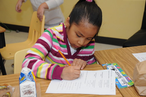 A student works hard on her assignment while eating a grab 'n' go breakfast in Mikelle Caine's second grade advance class at Lake Forest Elementary School, Sandy Springs, Ga., (USDA photo by Debbie Smoot).