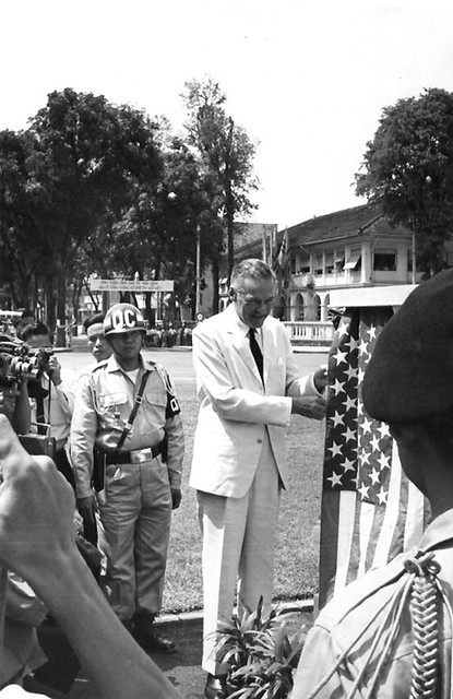 Ambassador Lodge touching an American flag with a Saigon police officer standing behind him.