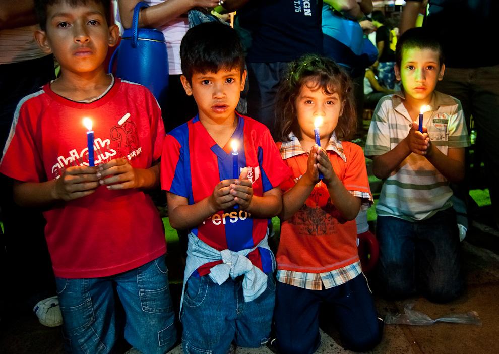 Cuatro niños se arrodillaban con sus velas encendidas frente a la capilla lateral de la basílica de Caacupé durante los rezos en la víspera del 8 de Diciembre. (Elton Núñez)