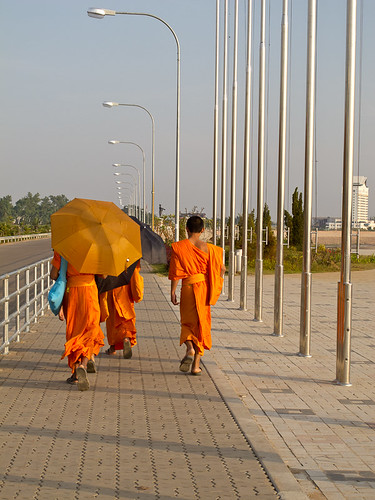 Monks walking by Mekong