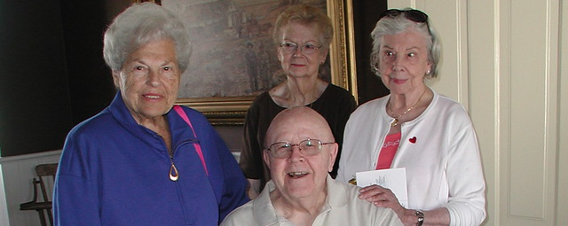 Three mature women and one mature man posing for a group shot in the dining room