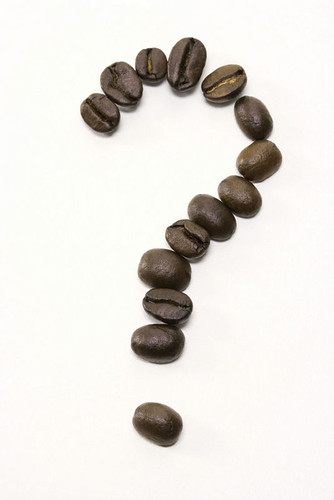 Question mark spelled out in coffee beans on white background.