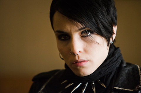 Lisbeth Salander, a white woman with short black hair, looks just off camera. She is wearing eyeliner.