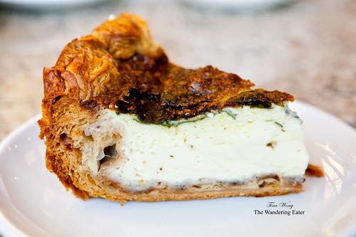 Slice of warm deep-dish cheddar and arugula quiche