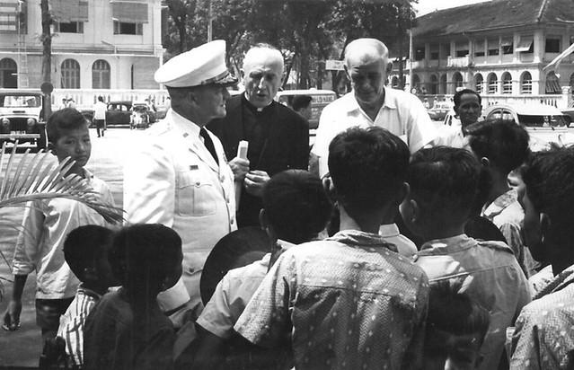 Vietnamese boys gathered around a Navy officer and a Catholic priest.