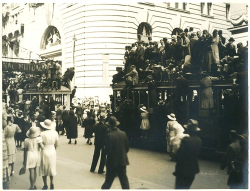 Spectators of the Australian Sesquicentenary parade stand on trams for a better view, George Street, Sydney, 26 January 1938 / photographer Donald Charles Boulton Maclurcan