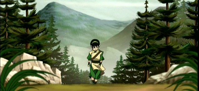 A landscape picture of a forest with mountains in the background. Toph's small figure in the middle coming up the trail still seems very bold and powerful. She is solitary, but in stride and determined.