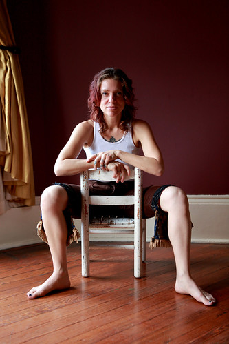 A picture of Ani Difranco sitting backwards on a chair in a red room facing hte camera.
