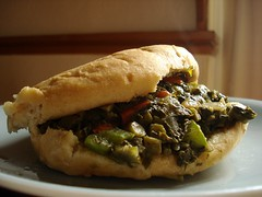 A soft white bread roll filled with a mixture of cooked dark leafy greens, chopped onion, and diced peppers. It sits on a pale blue plate, with sunlight falling in from the right.