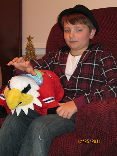 12/25/11: Wearing his new hat, and holding mom's Weagle pillow pet