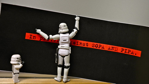 Two stormtrooper figurines putting up a sign reading 'In protest against SOPA and PIPA'