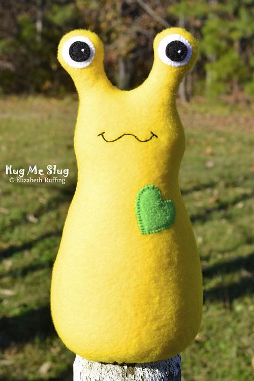 Bright yellow fleece Hug Me Slug art toy by Elizabeth Ruffing