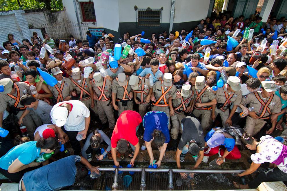 Centenares de peregrinantes luchaban para obtener un poco de las milagrosas aguas del Tupãsy Ykua, un manantial que brota a pocas cuadras de la Basílica. Por momentos la policía tuvo que luchar contra la multitud que casi llegó a desbordarse. (Tetsu Espósito)