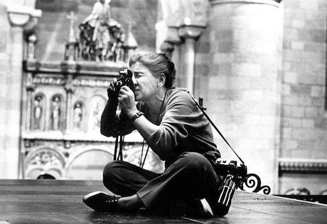 Eve Arnold sits cross-legged on the floor looking through a camera lens