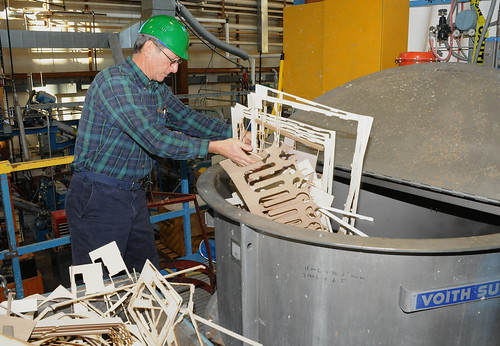 U.S. Forest Service Forest Products Lab researcher John Hunt loads recycled panel scraps into a tank where it will be broken down and used to press a new board. (U.S. Forest Service)