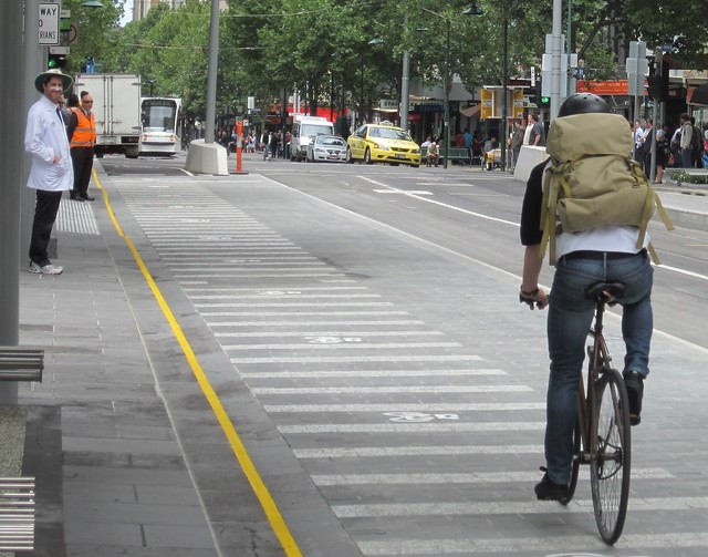 Cyclist rides along the new tram stop/bike lane
