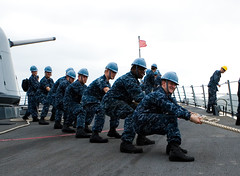 In this file photo, linehandlers aboard USS Milius (DDG 69) heave around on a ship's mooring line as the ship arrives in Guam Jan. 28.  (U.S. Navy photo by Lt.j.g. David Gardner)