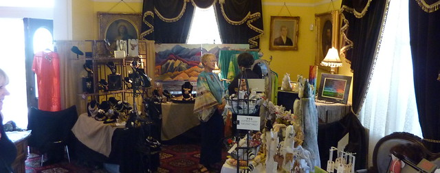 photo of woman in front of crafts and jewelry at a craft fair at the Lake Mansion
