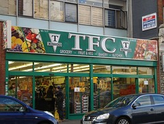 "A wide terraced shopfront with a fully glazed frontage surrounded by green framing.  The interior is filled with customers, sacks of onions, and boxes of grocery items.  The sign above reads ""TFC / grocery / fruit & veg / bakery / butcher""."