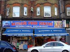 "A mid-terrace shop stretching over two shopfronts, with pallets of fruit and vegetables stacked outside on the pavement.  The sign at the top of the frontage is blue, with red and white letters reading ""Beydağı Food Centre / International Supermarket"".  A blue canopy stretches over the pavement pallets, with white letters reading ""Butchery & Bakery / Turkish - Greek - English - Polish Products""."