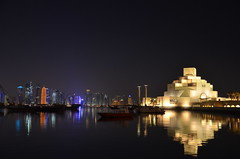 The museum of Islamic Art at night, with the Doha skyline just behind.`