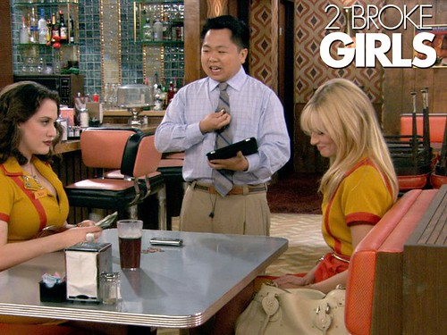 Han, the Asian owner of the diner where the 2 Broke Girls work, talks to them while they sit in a booth