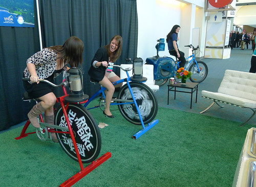 women in dress clothes generate power by pedaling bikes at a conference
