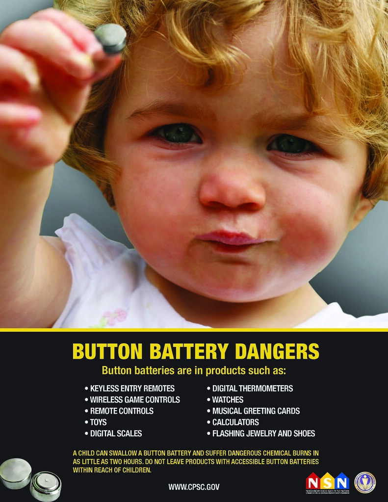toddler holding a coin-sized battery