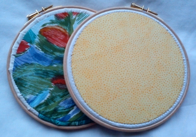 The backs of the embroidery pieces, neatly finished with a circle of cotton
