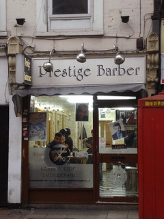 "A small, narrow terraced shopfront with a sign above reading ""Prestige Barber"" in grey letters outlined in black, on a white background. The shopfront is fully glazed, with a brown wooden framework. The interior is lit up and a few people are just visible inside. Part of a red telephone box can be seen to the right on the pavement outside."