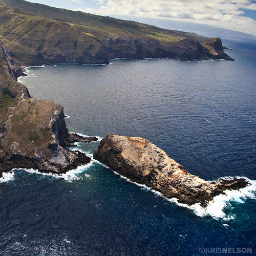 Cliffs and small islands made from ancient lava jets up through the ocean's surface.