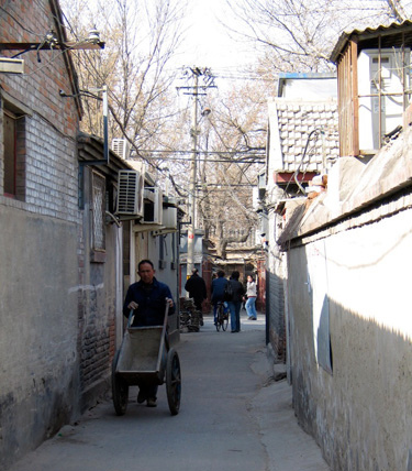 Man pushing an empty cart through shaded narrow street