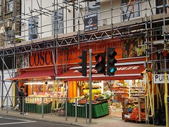 A terraced double-width shopfront with vegetable displays at the front and packaged goods visible on shelves inside.  The building is covered with scaffolding.