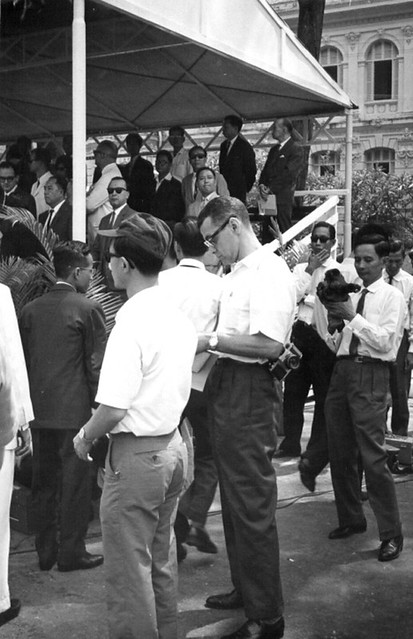 Americans and Vietnamese standing under a tent on bleachers