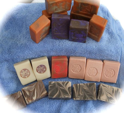 19 soaps ranges on a blue towel. There are pink, pink/purple swirls, white with purple mica flower stamp, orange/brown swirls, brown/white swirls, purple/brown swirls.