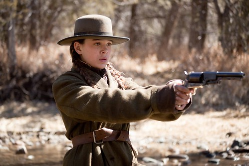 young Mattie Ross holding a gun and wearing a wide-brimmed hat