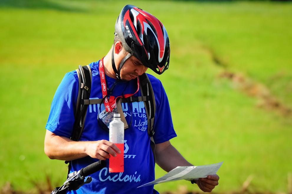 Un participante revisa su mapa mientras se hidrata poco antes de la charla inicial para comenzar la carrera, el evento tuvo más de 350 inscriptos en las categorías de trekking y ciclismo. (Elton Núñez)