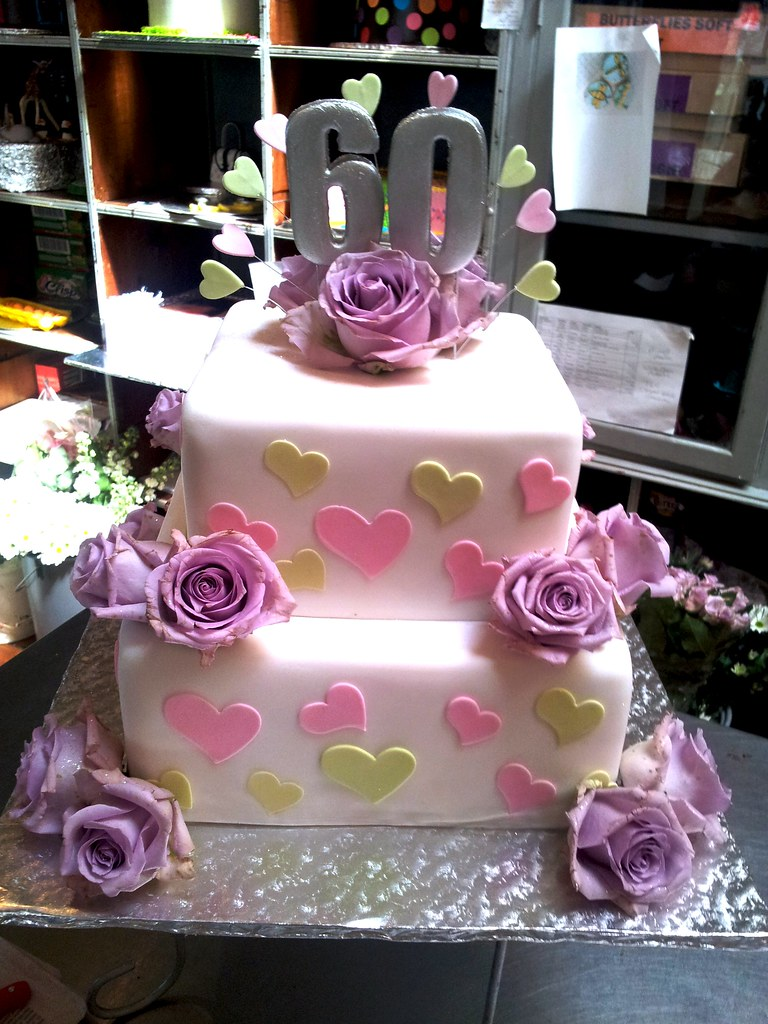 2 Tier Square Wicked Chocolate Cake Covered In White Fondant Icing Decorated With Pastel