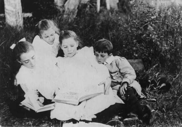 Group of children sitting on the grass reading books, 1900-1910