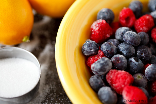 bowl of blueberries and raspberries next to some lemons