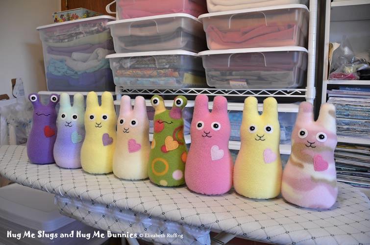 Fleece Hug Me Slugs and Hug Me Bunnies, all in a row, original art toys by Elizabeth Ruffing