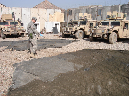 At a remote patrol base in Iraq, ARS scientist and U.S. Army entomologist Seth Britch applies a pesticide treatment to camouflage netting and shade cloth that will be suspended over outdoor eating and cooking areas and areas between dormitories. This treatment reduces populations of biting flies and mosquitoes by transferring lethal doses to the insects when they rest on the camouflage material.