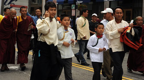 Tibetan men, boys, monks, in traditional clothes, robes, chubas, on the cell, marching, Happy Birthday to His Holiness the Dalai Lama Parade, Tibetans at Kalachakra, Washington D.C., USA by Wonderlane