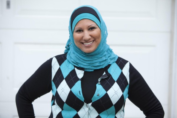 A woman from All American Muslim. She is giving a warm smile in front of a garage, and wearing a turquoise head scarf that compliments her plaid vest