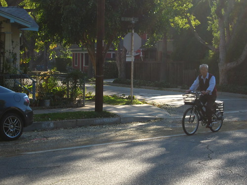 An older asian man rides a bike in El Centro Street bike lanes on a quiet Sunday afternoon