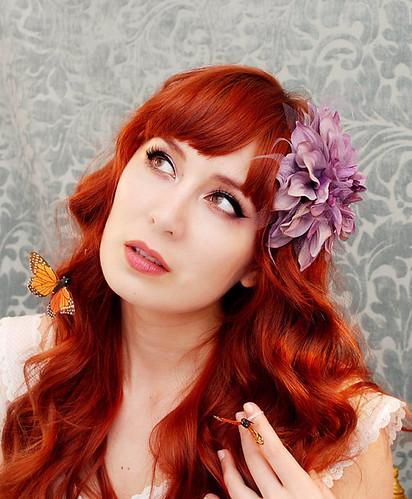 primo piano di ragazza con capelli rossi decorati con fiori