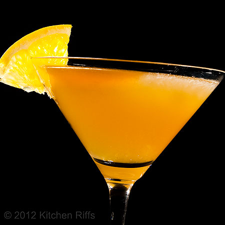 Sidecar Cocktail with orange wheel garnish, black background